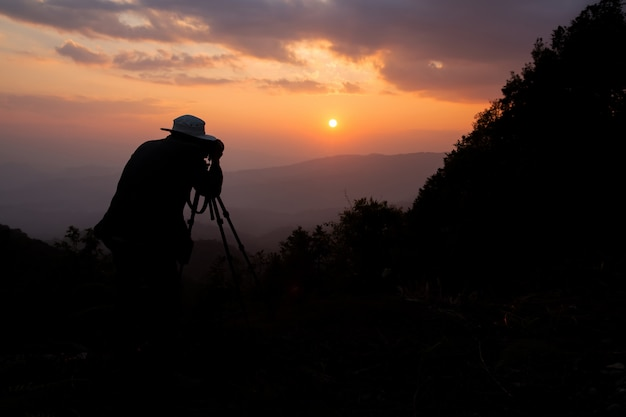 Silhouette d'un photographe qui tire un coucher de soleil dans les montagnes