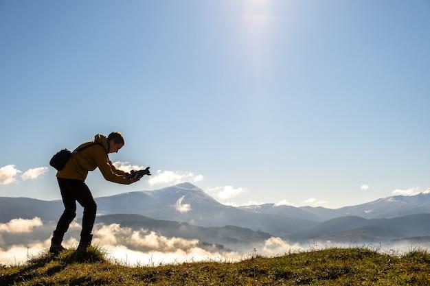 Silhouette d'un photographe de routard prenant des photos du paysage du matin dans les montagnes d'automne avec un appareil photo numérique.
