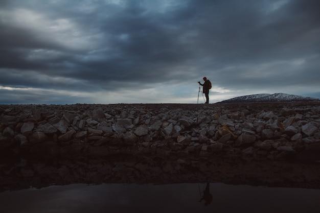 La silhouette d'un photographe avec un trépied se tient sur le rivage sur un fond de ciel nuageux