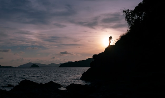 Silhouette d'un photographe ou d'un voyageur utilisant un appareil photo reflex professionnel