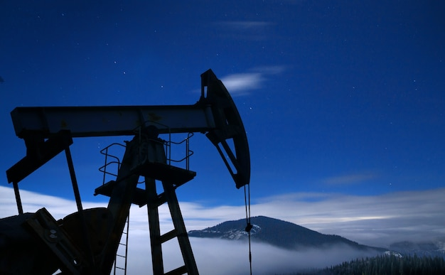 Silhouette de pompe à huile la nuit.