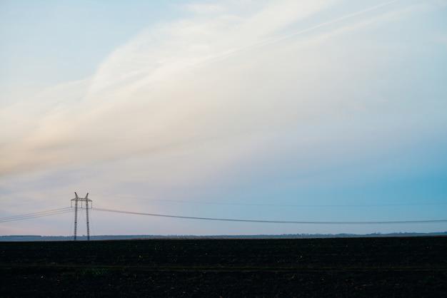 Silhouette de poteau électrique avec espace copie. fils de haute tension au-dessus du sol. l'industrie de l'électricité.