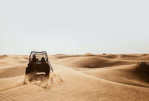 Silhouette de quad buggy bike à la dérive dans les dunes de sable safari du désert d'al awir, duba, émirats arabes unis