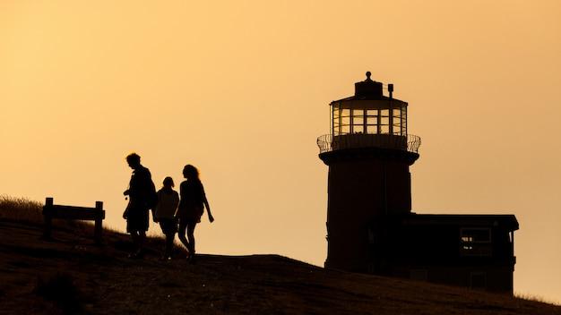 Silhouette de quelques personnes et d'un phare en angleterre