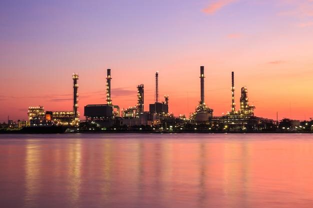Silhouette de raffinerie de pétrole le long de la rivière au lever du soleil (bangkok, thaïlande)