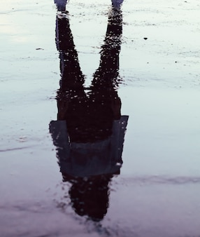 Silhouette réfléchie d'une fille dans une flaque d'eau au coucher du soleil
