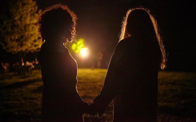 Silhouette rétroéclairée d'un couple de filles se tenant la main dans un jardin la nuit