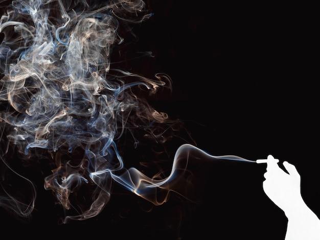 Silhouette rougeoyante d'une main avec une cigarette et de la fumée