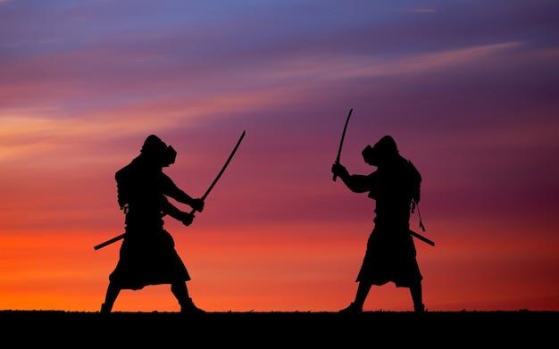 Silhouette de samouraïs en duel. photo avec deux samouraïs et ciel coucher de soleil