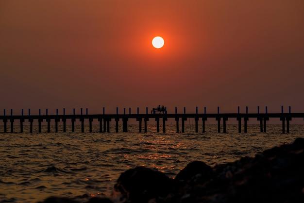 Silhouette le soir sur la plage ciel orange d'été