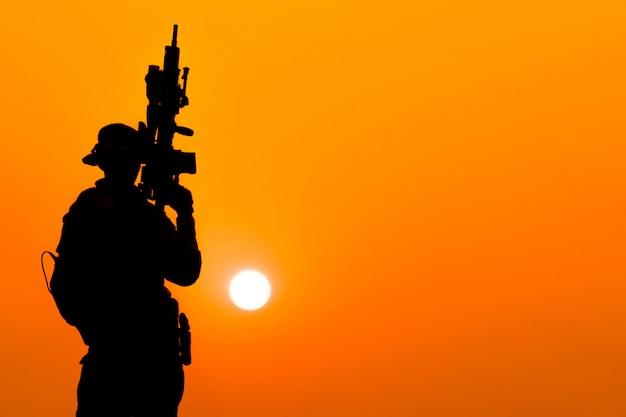 Silhouette de soldat dans le ciel coucher de soleil. soldat avec mitrailleuse patrouillant