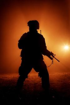 Silhouette de soldat d'infanterie moderne, combattant de l'armée d'élite en munitions tactiques et casque, debout avec un fusil de service d'assaut dans les mains