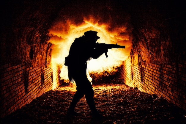Silhouette d'un soldat post-apocalyptique ou d'un survivant tirant avec une arme à feu automatique dans un donjon sombre, des tunnels d'égouts urbains ou un bunker souterrain avec feu d'explosion et fumée en arrière-plan