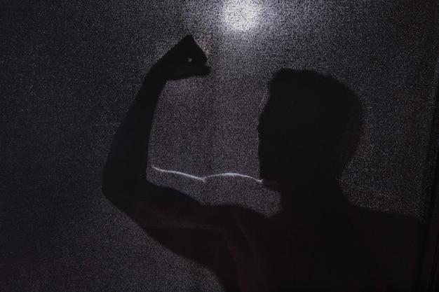 Silhouette sombre du mec montrant les biceps