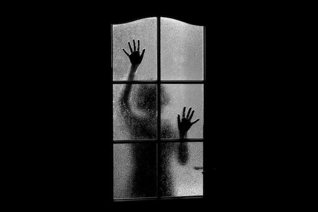 Silhouette sombre de la fille derrière la vitre