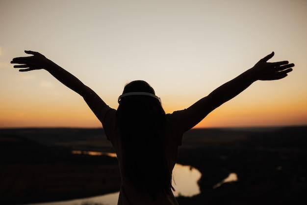 Silhouette sombre de jeune femme appréciant le beau coucher de soleil, vue arrière. concept d'été. copiez l'espace.
