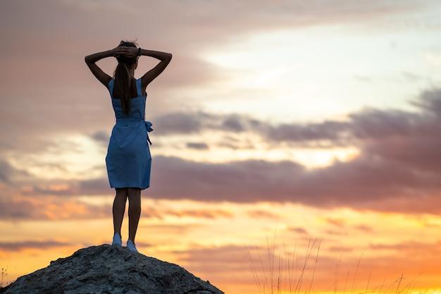 Silhouette sombre d'une jeune femme debout sur une pierre, profitant d'une vue sur le coucher du soleil à l'extérieur en été.