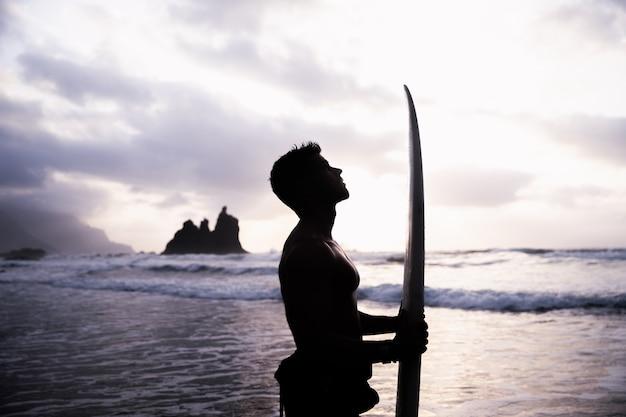 Silhouette d'un surfeur à la plage avec planche de surf à la main en regardant vers le ciel. personne en contact avec la nature, sportif concentré.
