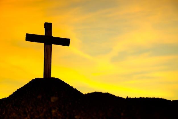 Silhouette de symbole de croix jaune dans la nature au coucher du soleil