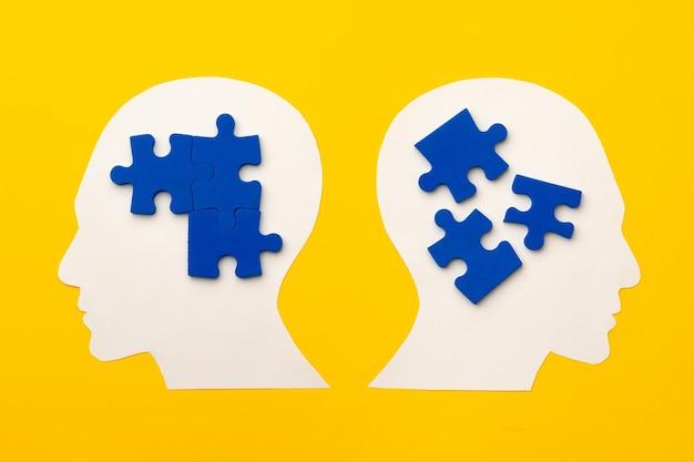 Silhouette de tête de papier découpé avec des pièces de puzzle sur fond jaune