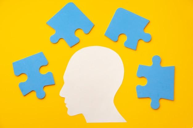 Silhouette de tête de papier découpé avec des pièces de puzzle sur jaune