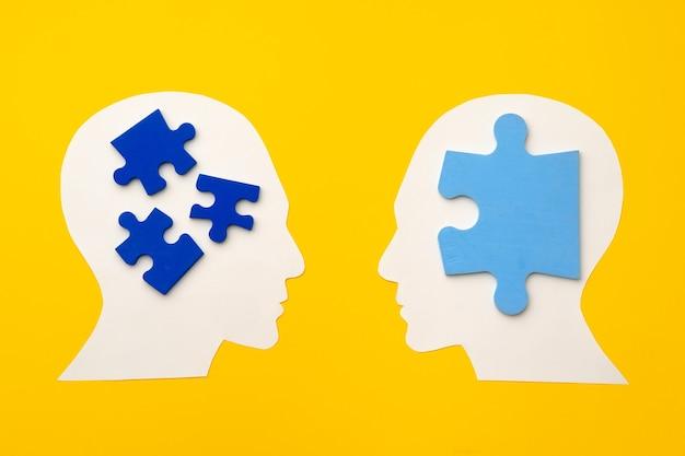 Silhouette de tête de papier découpé avec des pièces de puzzle sur une surface jaune