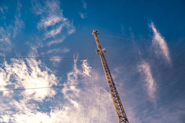 La silhouette d'une tour de télécommunications dans le contexte d'un ciel bleu incroyablement beau avec des nuages blancs brillants et flous