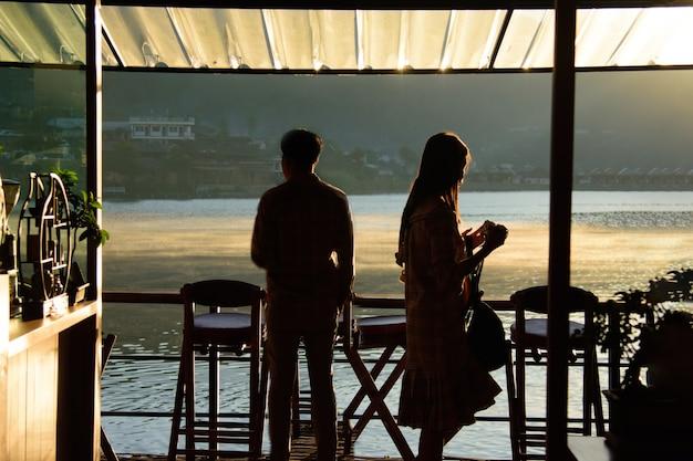 Silhouette d'un touriste debout dans la brume matinale dans un café en vue de rak thai village