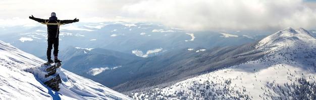 Silhouette d'un touriste seul debout au sommet d'une montagne enneigée dans une pose gagnante avec les mains levées, profitant de la vue et de la réussite par une belle journée d'hiver ensoleillée. aventure, activités de plein air, mode de vie sain.