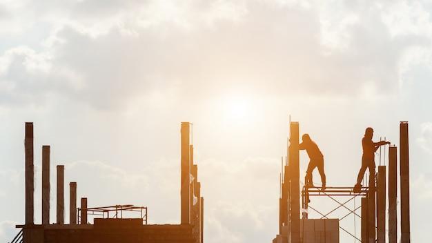 Silhouette de travailleurs de la construction travaillant sur place