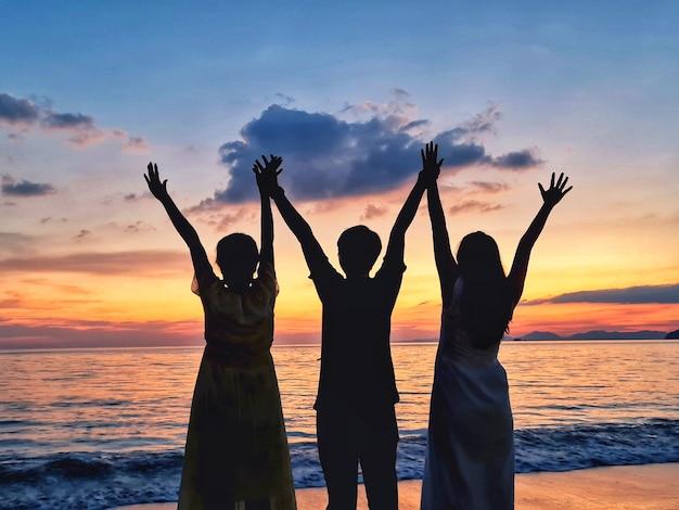 Silhouette de trois amis le soir à la plage en regardant le coucher du soleil.