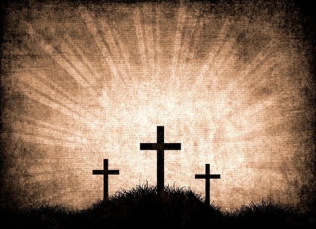 Silhouette de trois croix dans l'herbe sur un fond grunge