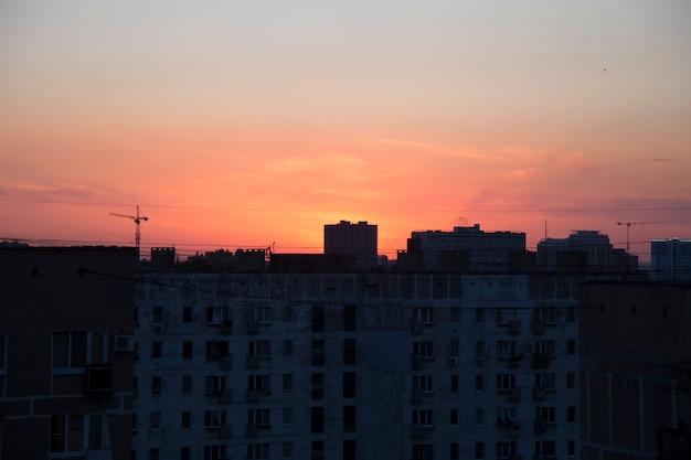 Silhouette urbaine noire contre un coucher de soleil orange