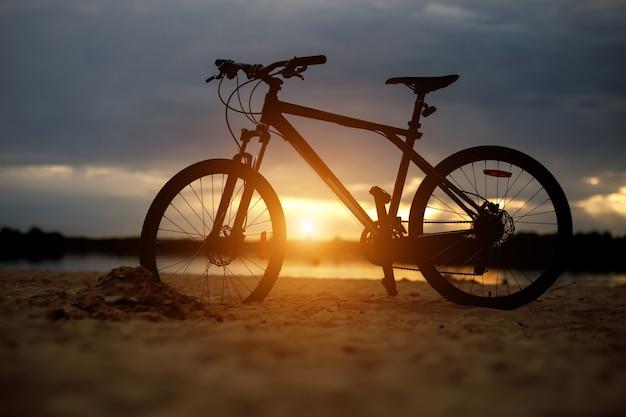 Silhouette de vélo de sport sur une plage. coucher de soleil.