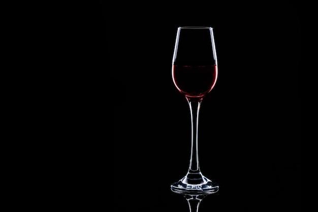 Silhouette en verre avec du vin rouge isolé sur fond noir