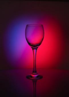 Silhouette de verre transparent sur fond rouge et violet