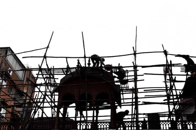 Silhouette de woker sur un échafaudage en bambou travaillant sur un chantier de construction.