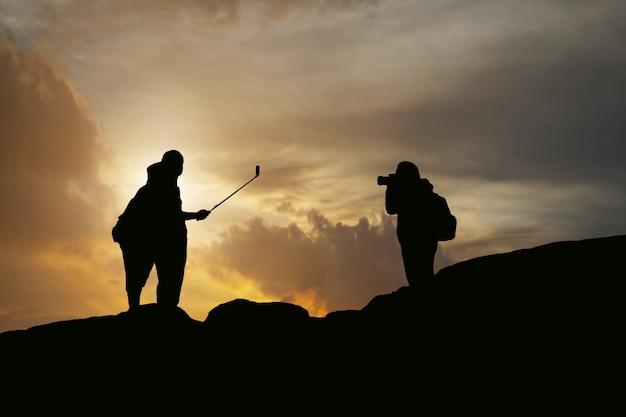 Silhouette de womem et de l'homme prennent la photographie et le selfie avec la montagne au coucher du soleil.