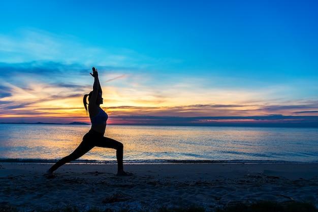 Silhouette de yoga femme de méditation sur l'océan pendant le coucher de soleil incroyable. fitness et mode de vie sain.