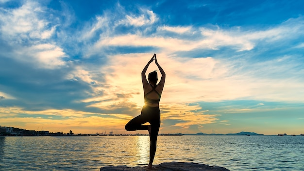 Silhouette de yoga femme de méditation sur l'océan pendant le coucher de soleil incroyable.