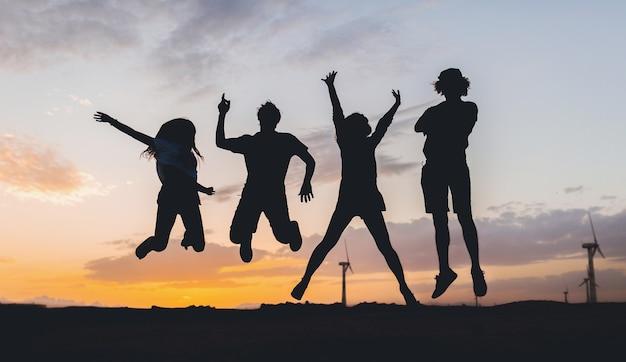 Silhouettes d'amis heureux sautant sur le coucher du soleil