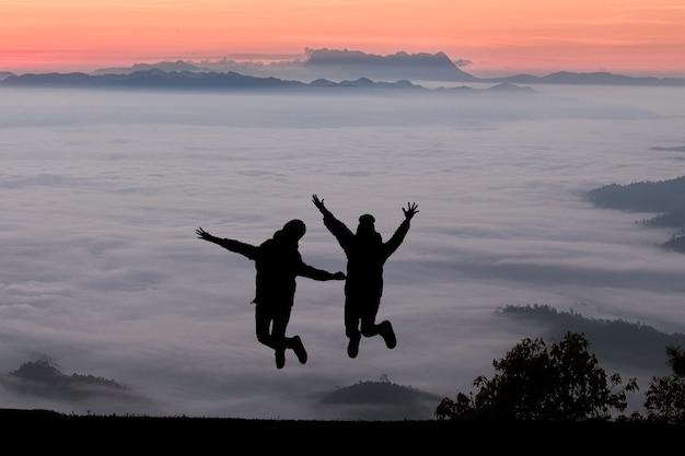 Silhouettes d'amis sautant sur le sommet de la montagne. sport et concept de vie active