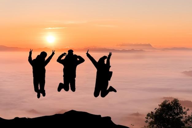 Silhouettes D'amis Sautant Sur Le Sommet De La Montagne. Sport Et Concept De Vie Active Photo Premium