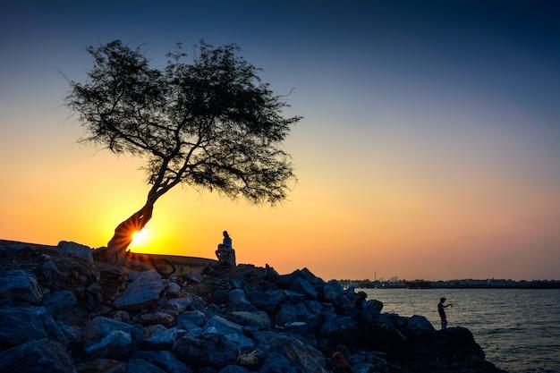 Silhouettes au coucher du soleil beau couloir du soir s'étend dans la mer.