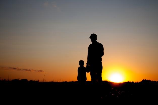 Silhouettes au coucher du soleil père et fils. heure d'été