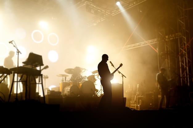 Silhouettes de bandes sur un chanteur concer avec guitare