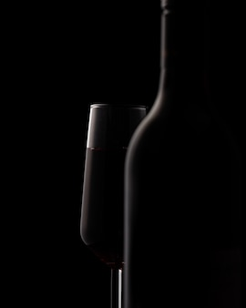 Silhouettes de bouteille de vin et verre à vin sur fond noir