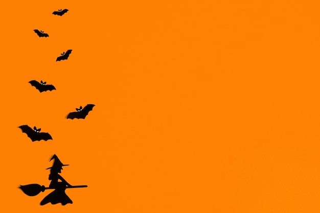 Silhouettes de chauves-souris en papier noir sur fond orange pour halloween