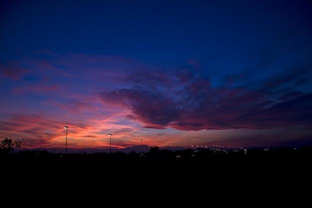 Silhouettes de collines et de réverbères sous un ciel nuageux pendant un beau coucher de soleil