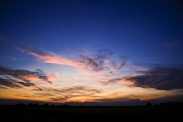 Silhouettes de collines sous un ciel nuageux pendant un beau coucher de soleil
